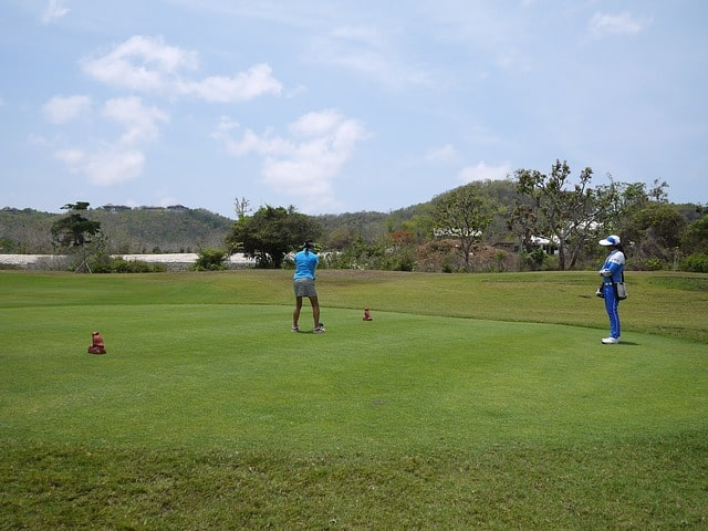 A golfer tees off in Bali.